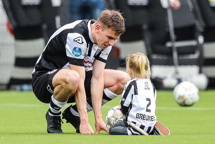 Tim Breukers en zijn dochtertje Jade op het veld van Erve Asito. Hij speelde zijn laatste duel voor Heracles in Almelo.