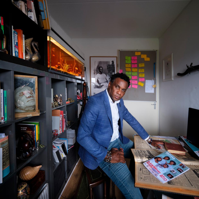 Marvin Hokstam, met op de achtergrond een portret van zijn betovergrootvader die in verzet ging tegen de slavernij.