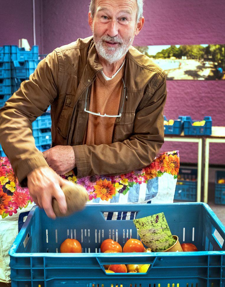 Karel Galenkamp neemt zijn pakket in ontvangst in Amsterdam-Noord. Beeld Patrick Post