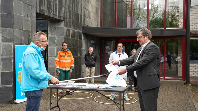 FNV'er Gerard Veldhuis (l) reikt Dethon directeur Edwin van den Berghen een nagenoeg leeg cao-boekje aan.