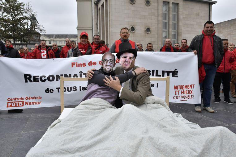 Betogers verkleed als premier Charles Michel en VBO-voorzitter Pieter Timmermans in bed, tijdens een actie van de vakbonden voor het hoofdkwartier van de werkgeversorganisatie in Brussel. Beeld BELGA