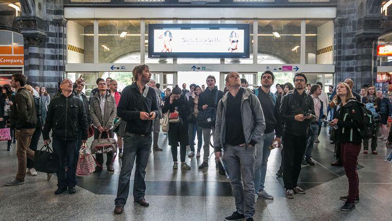 Treinreizigers wachten in het station Gent Sint-Pieters op meer info over afgeschafte treinen. Beeld Bas Bogaerts