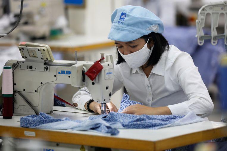 Een medewerker in een textielfabriek van Garment 10, een bedrijf dat vooral veel herenoverhemden maakt, in Hanoi (Vietnam). Beeld EPA