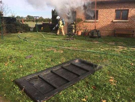 Een brandweerman bij het brandende huis.