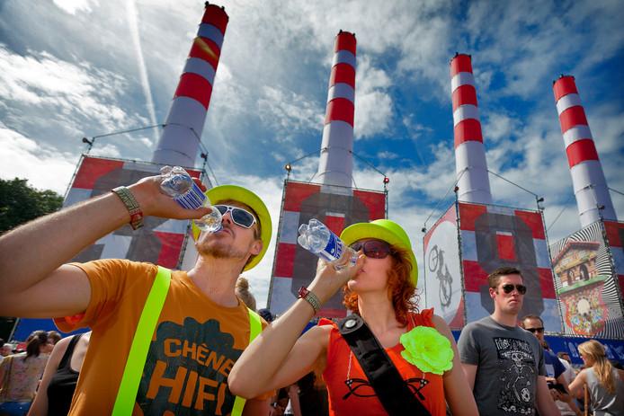 Festivalgangers met flesjes water op een snikhete dag.