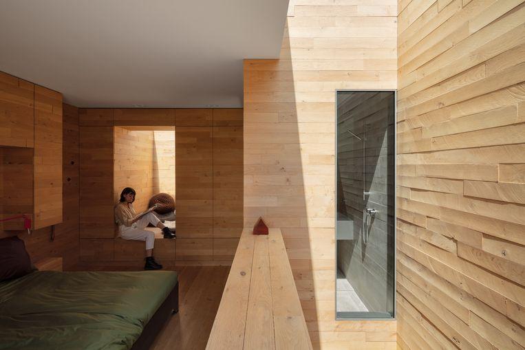 De dakkapel is dicht om inkijk te vermijden. Maar via de bovenzijde valt er toch licht binnen, zodat de slaapkamer baadt in een zachte gloed. Beeld Stijn Poelstra