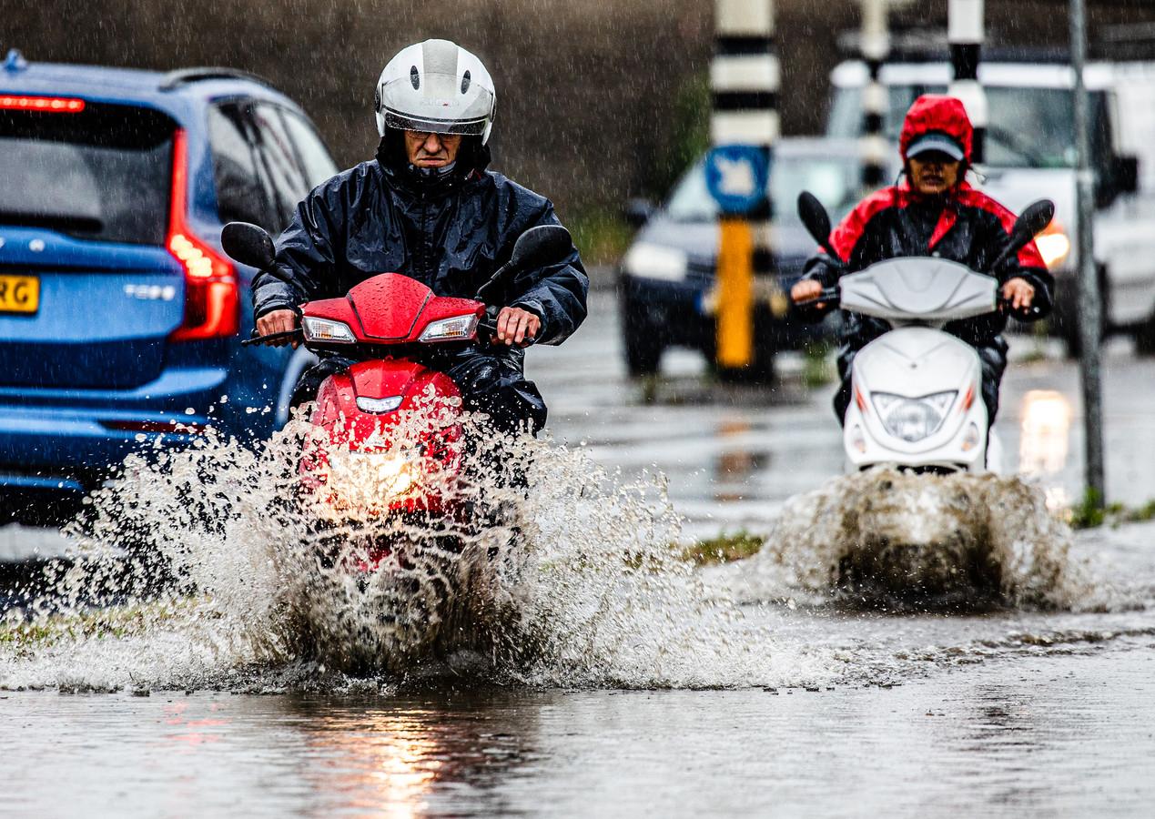 Een wolkbreuk in Dordrecht zorgt voor veel wateroverlast. Veel water op de wegen en fietspaden. Mensen banen zich een weg door de plassen.