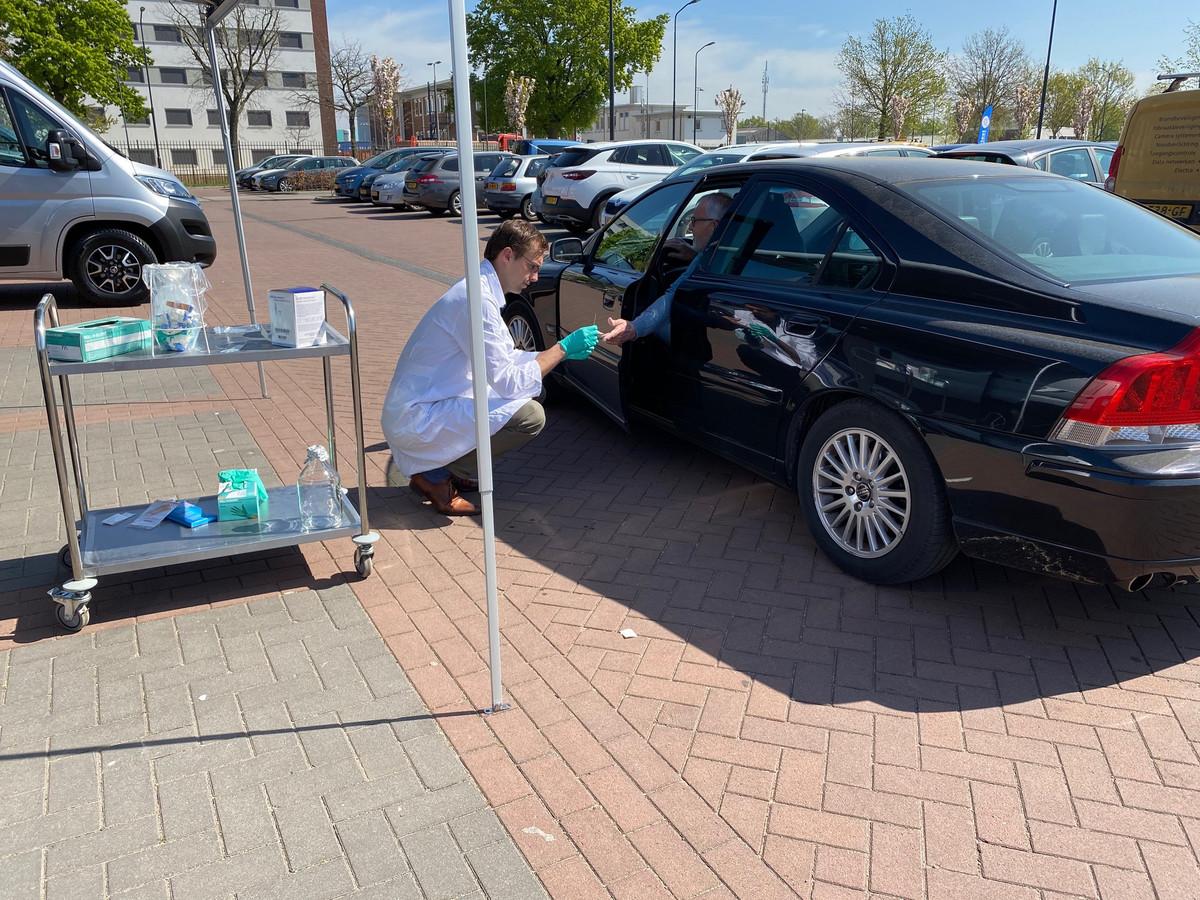 Deur op een kier, arm naar achteren en prik. Zo werkt het bij de mobiele prikpost voor mensen die denken dat ze corona hadden, op de parkeerplaats in Oss.