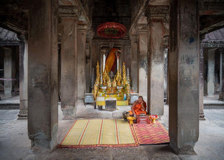 Een monnik biedt boeddhistische ceremonies aan in de lege tempel van Angkor Wat. Beeld Antoine Raab