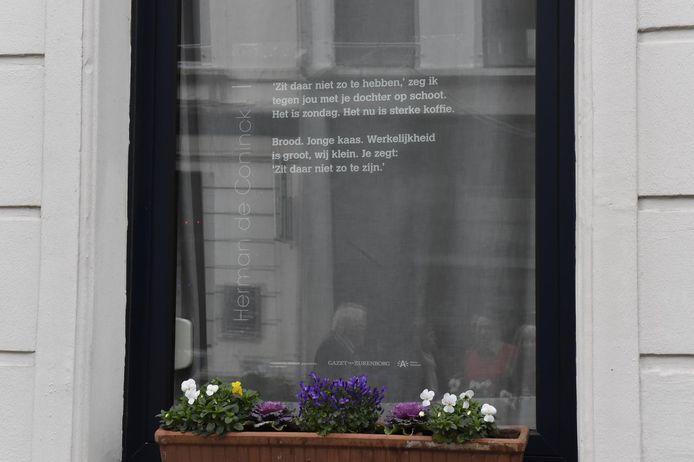 Een van de vele gedichten, hier op een venster op de Dageraadplaats.