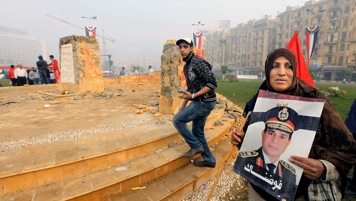 Een vrouw houdt een foto van generaal El-Sissi omhoog voor het vernielde monument op het Tahrirplein
