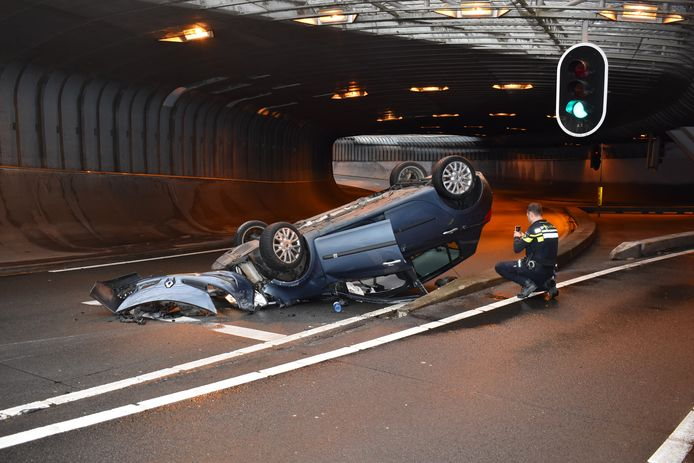 Een agent maakt foto's van het wrak van de over de kop geslagen auto in de Willemstunnel in Arnhem.