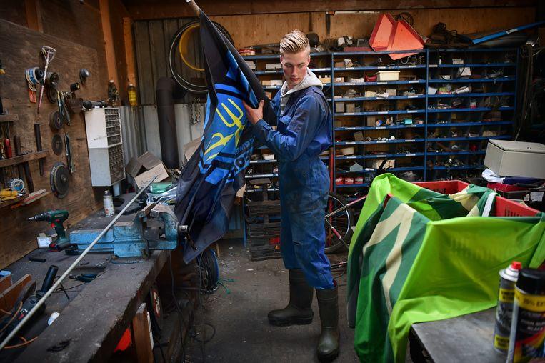 De vlag bij boer Geert wordt door zijn zoon gemaakt om achter op de wagen te monteren.  Beeld Marcel van den Bergh