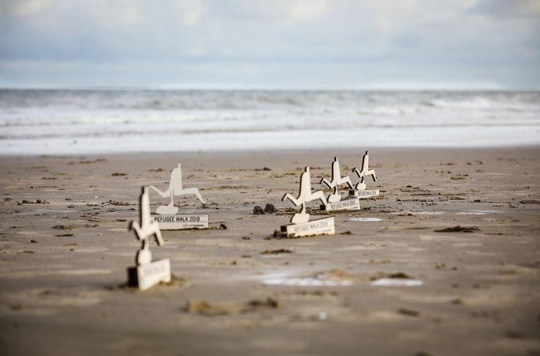 De mannetjes uit hout werden op het strand geplaatst door Vluchtelingenwerk Vlaanderen.