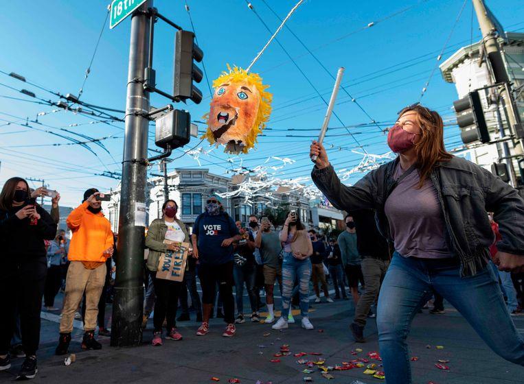 Een vrouw raakt een Trump-piñata in San Francisco. Beeld AFP