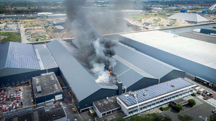 De brand woedt op het dak van de loods.