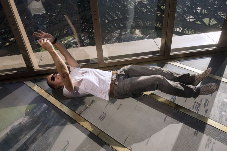 A visitor lies down to take a selfie on the new glass floor at the Eiffel Tower in Paris on October 3, 2014. The Eiffel Tower is inaugurating a new glass floor on October 6 that is turning the heads of the millions of tourists who flock to Paris's best-known landmark every year. AFP PHOTO LIONEL BONAVENTURE Beeld AFP