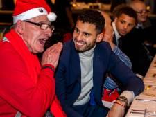 Adam Maher (26) en Kees (69) prikken samen een vorkje tijdens kerstdiner voor eenzame ouderen in stadion Galgenwaard