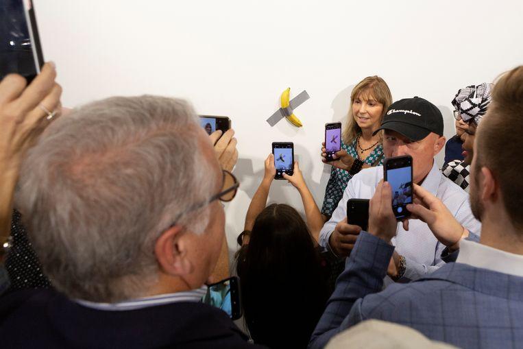 Een vrouw poseert bij een banaan die aan de muur geplakt werd met ducttape. De banaan van het kunstwerk 'Comedian' van Maurizio Cattelan werd vervangen omdat David Datuna de vorige leukweg opat. Beeld REUTERS