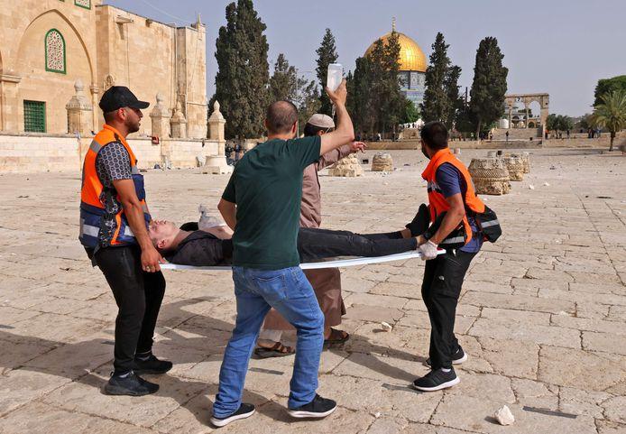 Palestijnse hulpverleners dragen aan het Moskeeplein een gewonde weg.