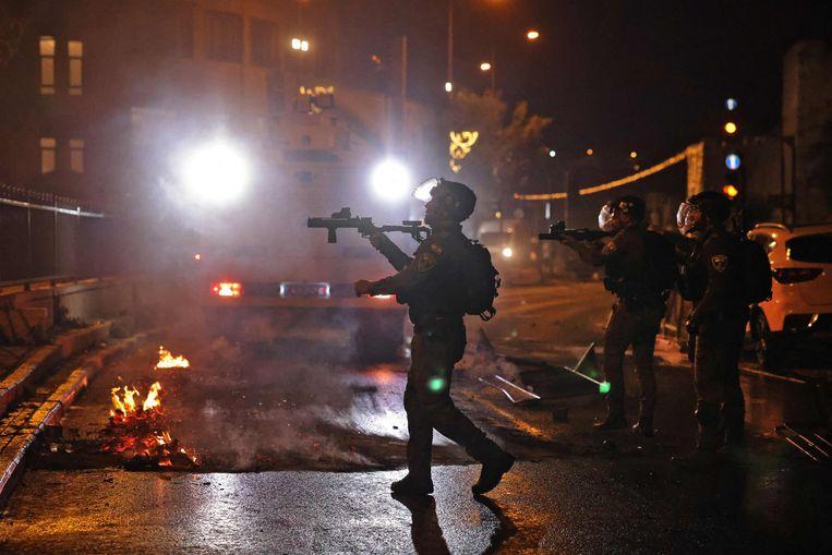Israëlische veiligheidstroepen verwijderen een brandende blokkade bij het oude centrum van Jeruzalem.  Beeld AFP
