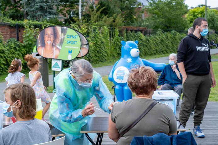 Aan een tafeltje in het park aan de Donkerlei krijgen de bewoners hun coronaprik.