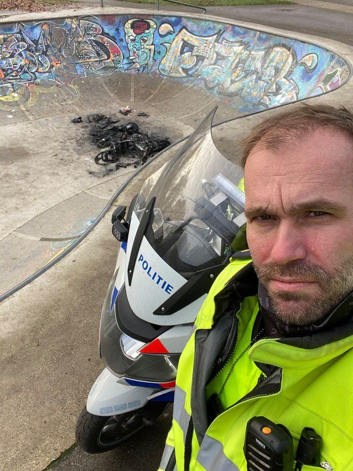 De wijkagent met op de achtergrond de verwoeste scooter.
