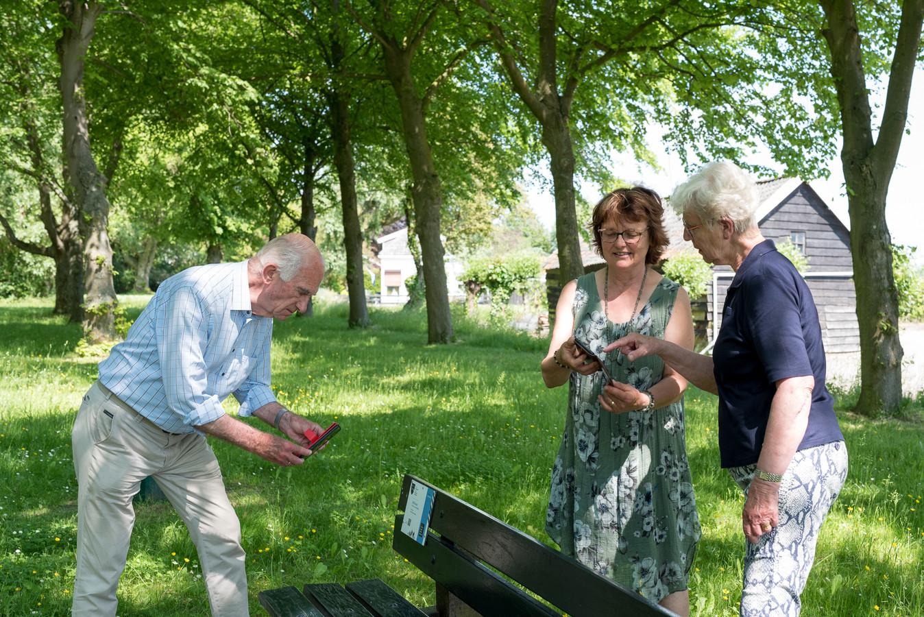 Adri Moelijker, Erna van der Spek en Riet Remeeus (vlnr) bij het bankje bij De Tol aan de Donkereweg in Schuddebeurs: één van de locaties waar een bordje met QR-code hangt.