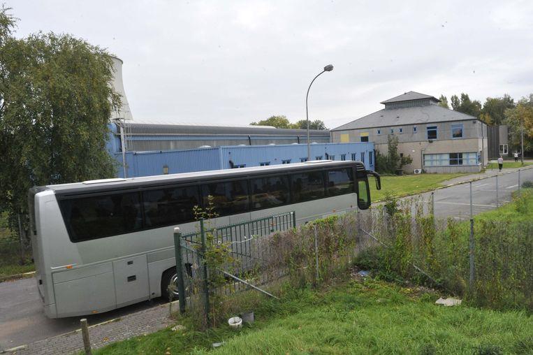 Een bus met vluchtelingen rijdt het opvangcentrum binnen.