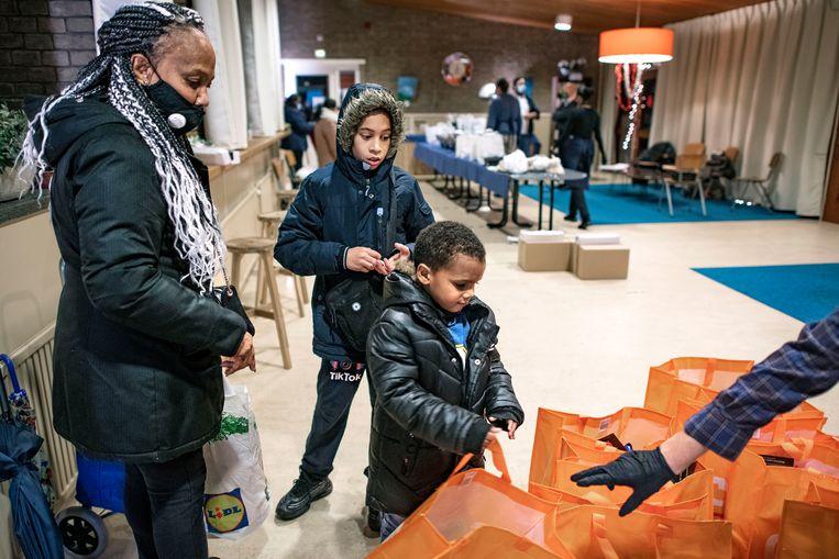 Tassen vol producten, van kerststol tot wasmiddel, worden in de Kerk van Nazarener uitgedeeld aan mensen die het moeilijk hebben.  Beeld Guus Dubbelman / de Volkskrant