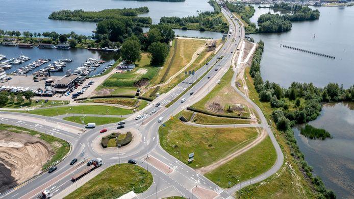 De aanleg van een nieuw fietspad onder de brug over het Veluwemeer had al klaar moeten zijn, maar heeft enige vertraging opgelopen. Nu zijn de werkzaamheden (links) volop bezig. De turborotonde verdwijnt, verkeer van Harderwijk naar Flevoland gaat in de toekomst onder het kruispunt door.