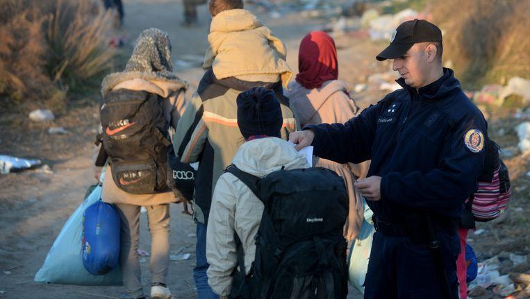 Servische agent controleert de documenten van vluchteling in de buurt van Tabanovce, op de grens van Macedonië en Servië. Beeld epa