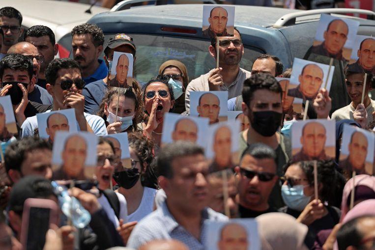 Honderden Palestijnen gingen donderdag in Hebron en Ramallah de straat op met foto's van de gedode activist. In Ramallah klonk de roep om het aftreden van president Mahmoud Abbas.  Beeld AFP