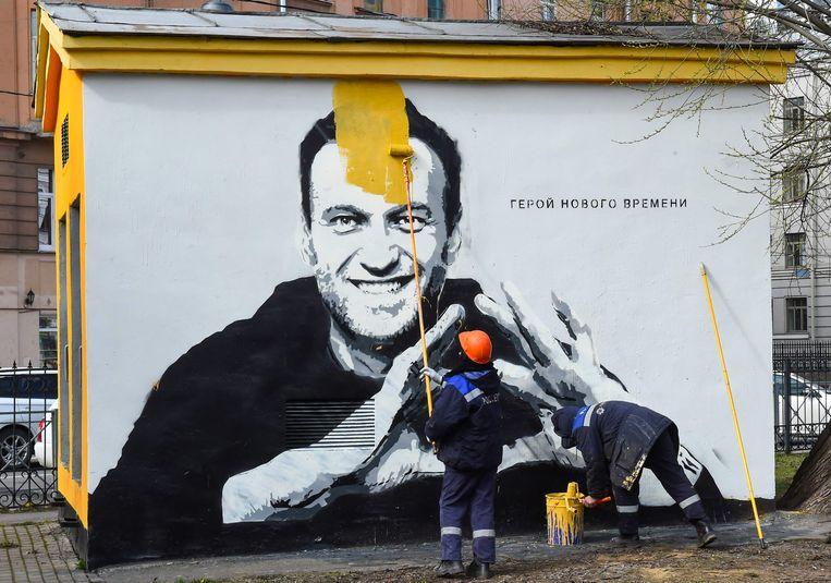 Een medewerker van een Russisch energiebedrijf schildert een portret van oppositieleider Aleksej Navalny over op een muur in Sint-Petersburg op 28 april 2021. Beeld AFP