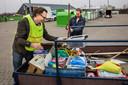 Dennis Happé (met bril) van Samen Circulair kijkt in de aanhangwagen of er nog spullen tussen zitten die hergebruikt kunnen worden.