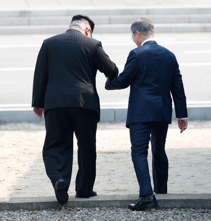 Moon helpt Kim Jong-un letterlijk over de drempel.