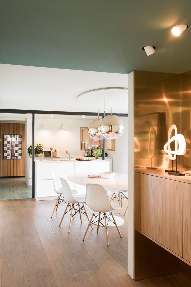 Witte eettafel van Eero Saarinen voor Knoll.De stoelen zijn van Charles en Ray Eames voor Vitra, de chromen hanglamp is van Tom Dixon. Beeld Verne