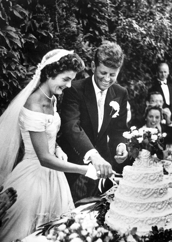 John F. Kennedy en Jacqueline Bouvier snijden de taart aan op hun huwelijksfeest op 12 september 1953. Het huwelijk weerhoudt JFK er niet van een rokkenjager te blijven, naar het voorbeeld van zijn vader. Beeld Hollandse Hoogte / EPA
