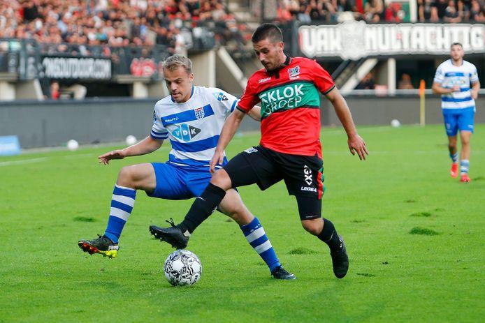 Jordy Bruijn schermt de bal af voor Thomas van den Belt in de wedstrijd tussen NEC en PEC Zwolle.