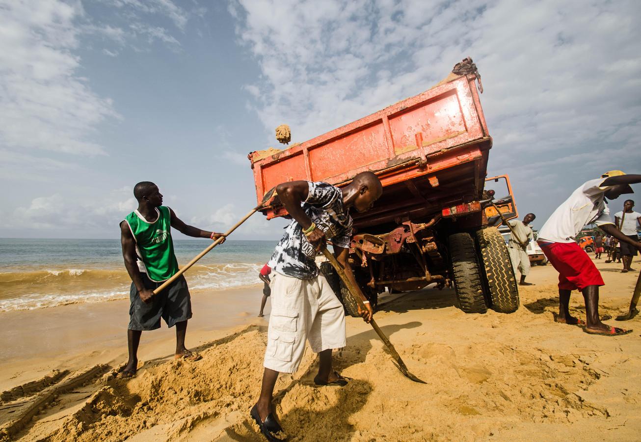 Illegale zandwinning op het strand bij Freetown in Sierra Leone.