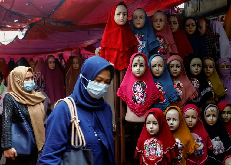 Vrouwen lopen langs een marktstal met jilbabs, islamitische hoofddoeken, in de Indonesische hoofdstad Jakarta. Beeld Reuters