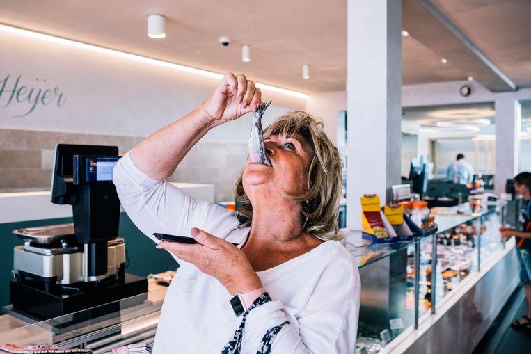 Een klant bij de viswinkel van Martin den Heijer in Rotterdam laat het zich smaken. Beeld null