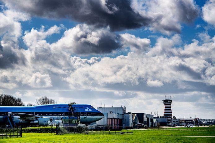 De verkeerstoren van Luchthaven Lelystad torent hoog boven het landschap uit. Rechts een KLM-vliegtuig op het terrein van luchtvaartthemapark Aviodrome.
