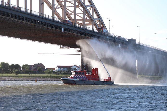 Een blusboot van de brandweer doet pogingen een brand aan het steigerwerk onder de Waalbrug bij Nijmegen te blussen.