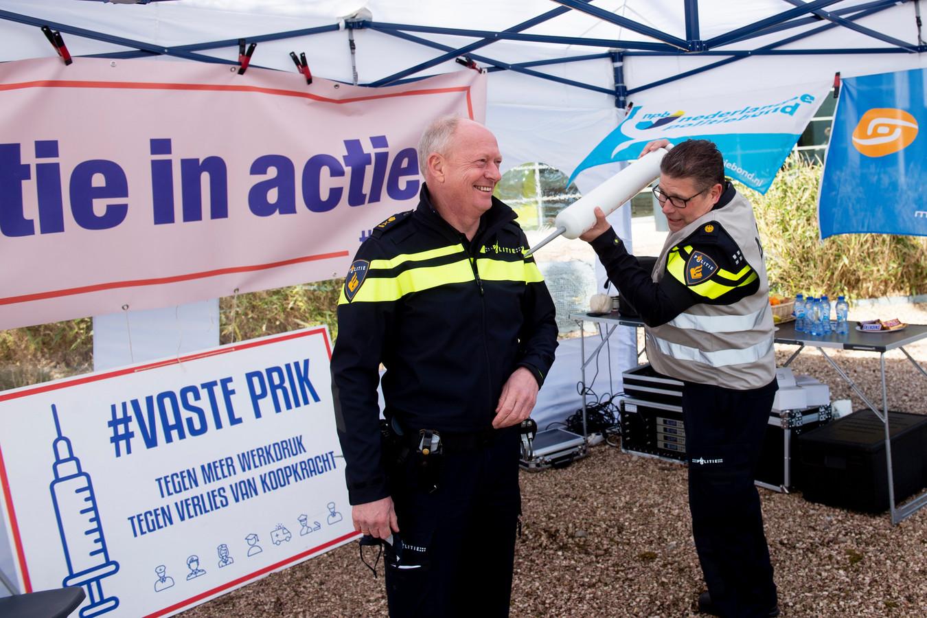 Ben Donkers zet de eerste prik bij hoofdcommissaris van de Regionale Politie Eenheid Oost-Nederland, Oscar Dros.