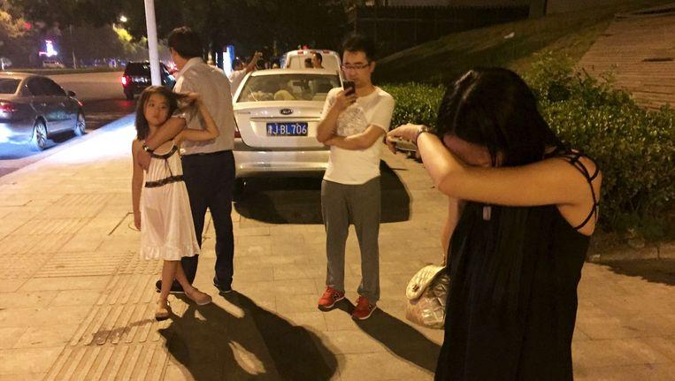 Chinezen op straat in Tianjin na de explosie. Beeld null