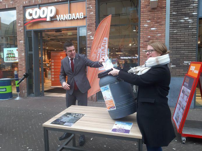 Wethouder Van Mierlo deponeert zijn kaart in de bus bij de Coop. Rechts Ruth Dam van de Stichting Present.