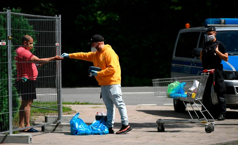 Op een parkeerplaats worden boodschappen aangeboden aan werknemers van Tönnies. Beeld AFP