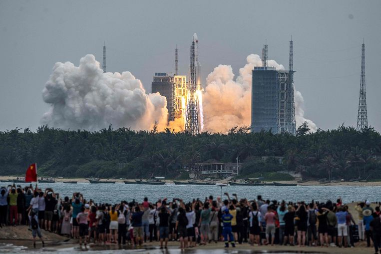 Mensen kijken toe hoe module Tianhe aan boord van de krachtige Lange Mars 5b-raket naar zijn baan om de aarde vertrekt.  Beeld AFP