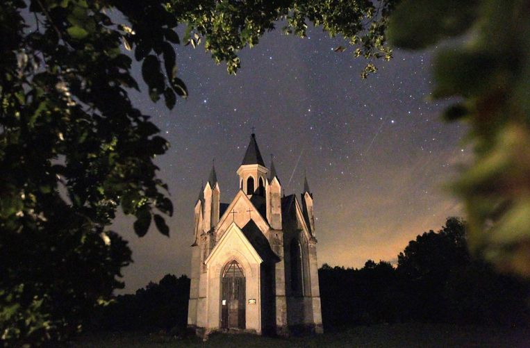 epa03822572 Meteors of the Perseids meteor shower burn up in the atmosphere behind a Catholic church near the village of Bogushevichi, some 100 km from Minsk, Belarus, late 12 August 2013. The Perseid meteor shower occurs every year in August when the Earth passes through debris and dust of the Swift-Tuttle comet.  EPA/TATYANA ZENKOVICH Beeld EPA